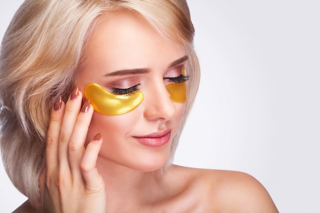 Beautiful woman with gold hydrogel patches