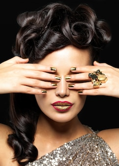 金色の爪と創造的な口紅を持つ美しい女性。黒い壁にスタイルの髪型を持つブルネットの女の子モデル