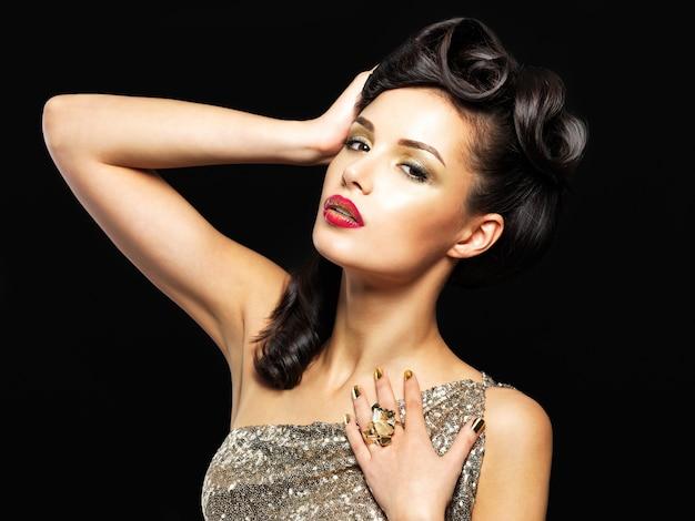 金色の爪と目のファッションメイクを持つ美しい女性。黒い壁にスタイルの髪型を持つブルネットの女の子モデル