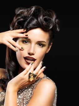 金色の爪と目のファッションメイクを持つ美しい女性。