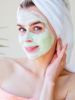 緑の自然な顔の粘土のマスクを持つ美しい女性。クローズアップの肖像画。彼女の顔に触れます。