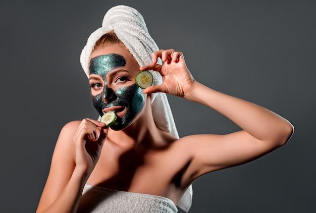 灰色の壁に緑の剥離マスクを持つ美しい女性。