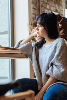 식당에서 멀리 보고 턱에 손으로 아름 다운 여자. 카페 테이블에 앉아서 책을 읽는 젊은 예쁜 여성의 사진.