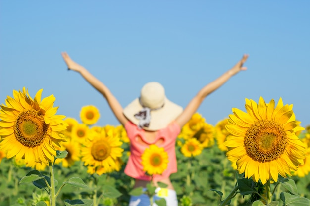 Beautiful woman with hat on her head in sunflowers field