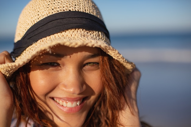 Beautiful woman with hat looking at camera on beach in the sunshine