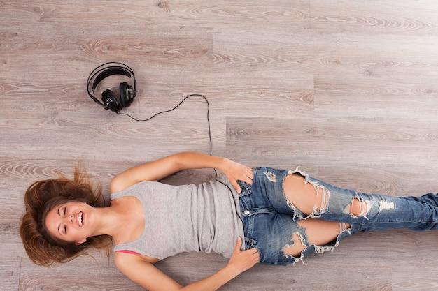 Beautiful woman with headphones lying on the floor