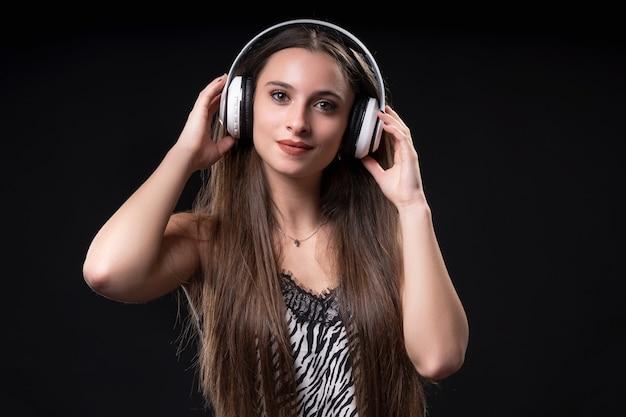 黒の背景にヘッドフォンを持つ美しい女性