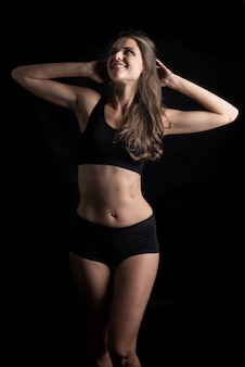 Beautiful woman with healthy body on black background