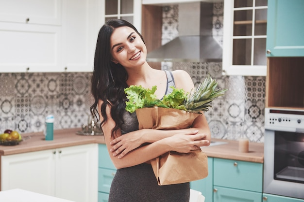 Beautiful woman with healthy food fruit in the kitchen.