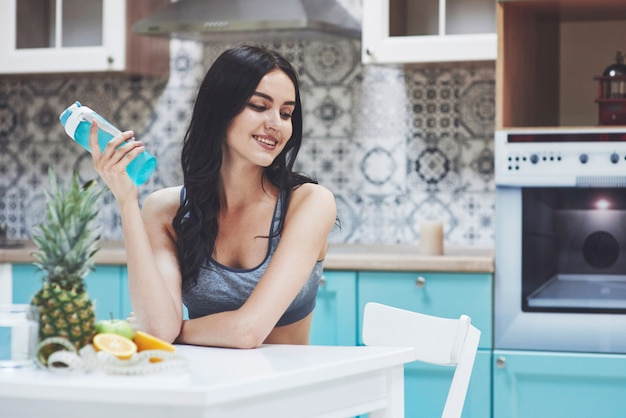 Beautiful woman with healthy food fruit in the kitchen