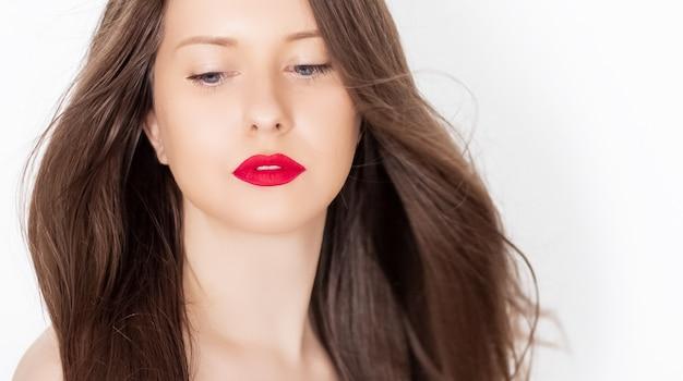 Красивая женщина со здоровыми шикарными длинными волосами, естественной брюнеткой с прической и красной помадой ...