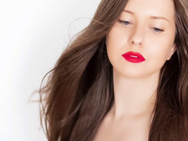 Beautiful woman with healthy gorgeous long hair natural brunette hairstyle and red lipstick makeup h...