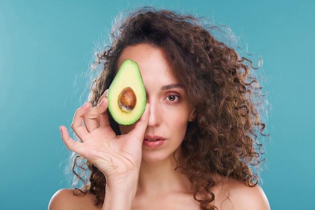 Красивая женщина со здоровой кожей и роскошными волнистыми волосами смотрит на вас левым глазом, держа половину свежего авокадо рядом с другим