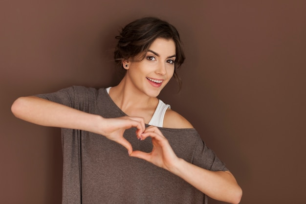 Beautiful woman with heart sign