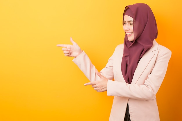 Beautiful woman with hijab on yellow background