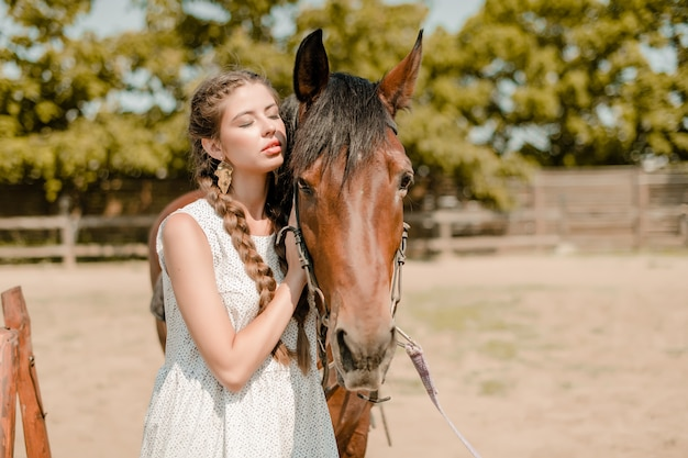 Beautiful woman with a horse on a ranch in a countryside