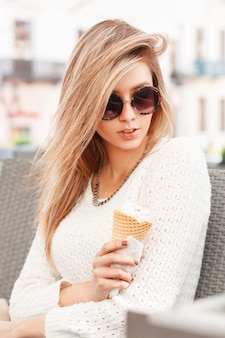 Красивая женщина с мороженым, сидя в летнем кафе