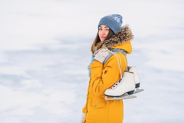 Красивая женщина с коньками посреди замерзшего озера