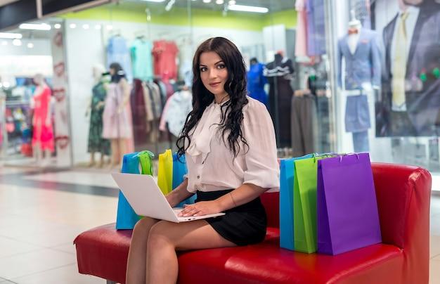 노트북 및 쇼핑몰에서 쇼핑 가방을 가진 아름 다운 여자