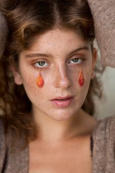 彼女の顔に葉を持つ美しい女性
