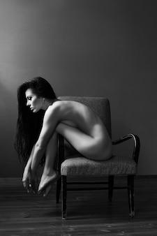 긴 검은 머리를 가진 아름 다운 여자는의 자에 앉는 다. 피부가 부드럽고 깨끗하며 다리가 길다. 소녀는 저녁에 의자에서 사랑하는 사람을 기다리고 있습니다.