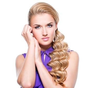 긴 금발 곱슬 머리와 얼굴-흰 벽에 고립 근처 손으로 아름 다운 여자.