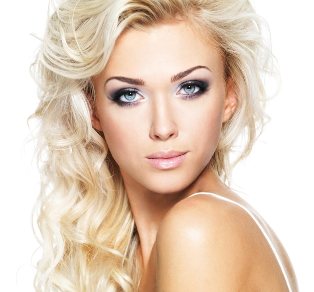 Beautiful woman with long blond curly hair. portrait of fashion model with bright makeup. isolated on white