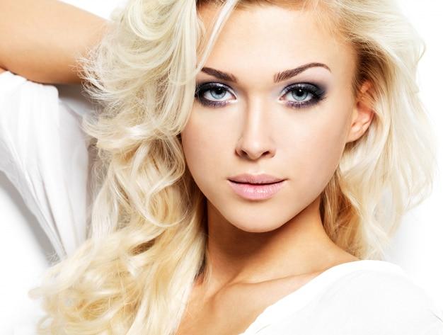 長いブロンドの巻き毛を持つ美しい女性。明るい化粧とファッションモデルの肖像画。白で隔離