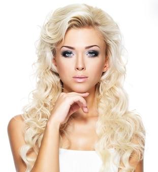긴 금발 곱슬 머리를 가진 아름 다운 여자입니다. 밝은 화장과 패션 모델의 초상화입니다. 흰색 절연