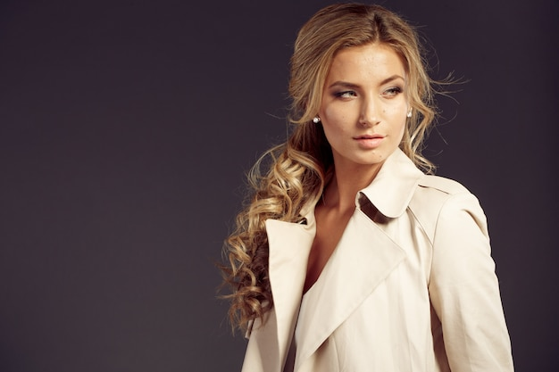 Beautiful woman with long blond hair in beige fur coat