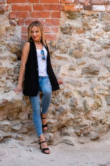 A beautiful woman  with long blond hair, a white blouse and blue jeaans  by the stone wall of the old town