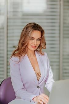 Красивая женщина с длинными вьющимися волосами в фиолетовой куртке работает на белом ноутбуке в офисе
