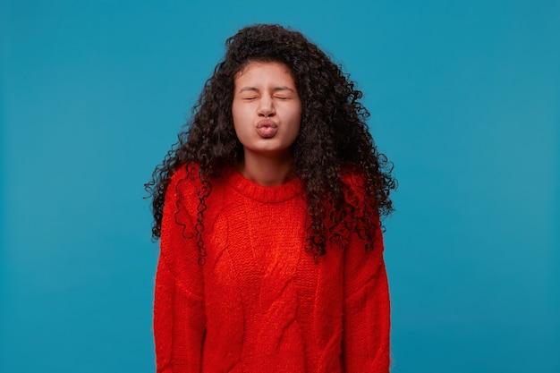 青いスタジオの壁に分離された赤いニットセーターの長い暗い巻き毛のウェーブのかかった髪を持つ美しい女性