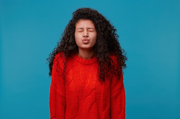 Beautiful woman with long dark curly wavy hair in red knitted sweater isolated over blue studio wall