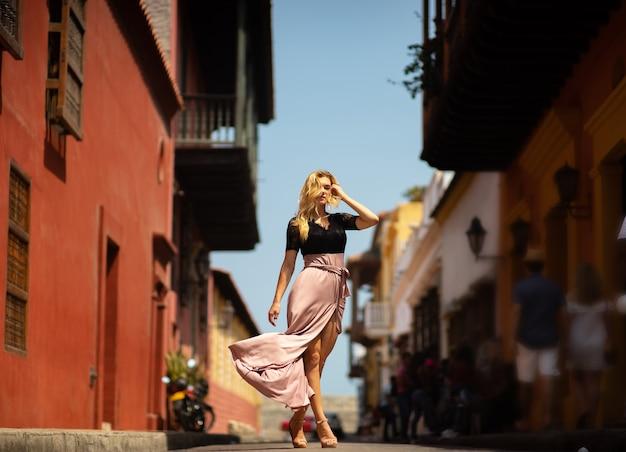 식민 벽으로 둘러싸인 도시 카르타헤나의 다채로운 거리에서 혼자 걷는 긴 드레스와 아름 다운 여자. 콜롬비아. 프리미엄 사진