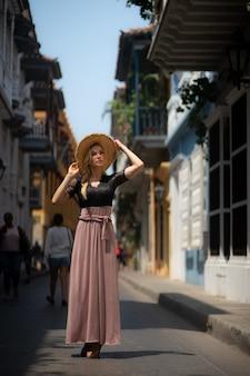 식민 벽으로 둘러싸인 도시 카르타헤나의 다채로운 거리에서 혼자 걷는 긴 드레스와 아름 다운 여자. 콜롬비아.