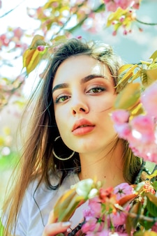 Beautiful woman with long hair enjoys the beauty of spring