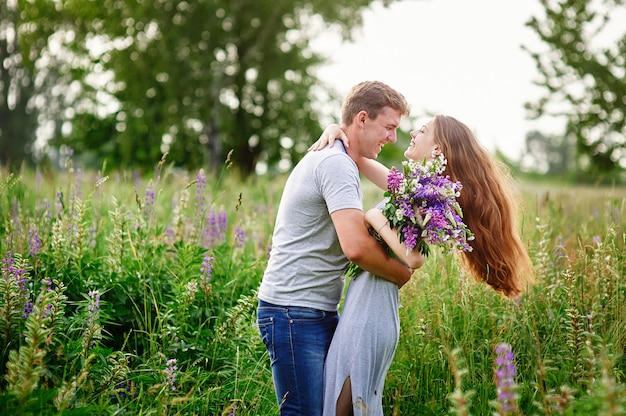 Beautiful woman with long hair and a happy man hugging in field