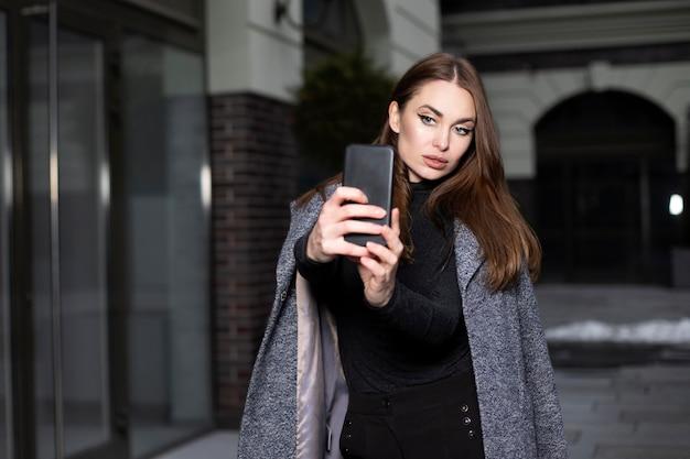 긴 머리를 가진 아름 다운 여자는 그의 손에 전화를 보유 하 고 selfie를 걸립니다. 모델 외모의 여성은 회색 코트와 검은 색 점퍼를 입고 있습니다. 여자가 전화로 말한다.