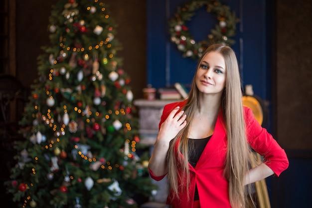 Красивая женщина с длинными волосами в красном костюме возле украшенного дерева и камина в темном интерьере