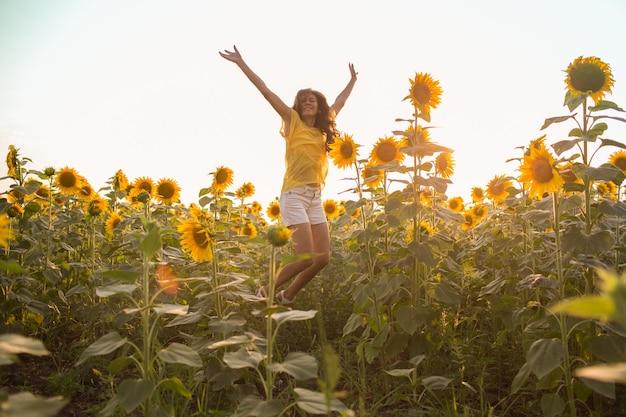 여름 햇살 아래 해바라기 밭에서 흰 드레스를 입은 긴 머리를 한 아름다운 여자