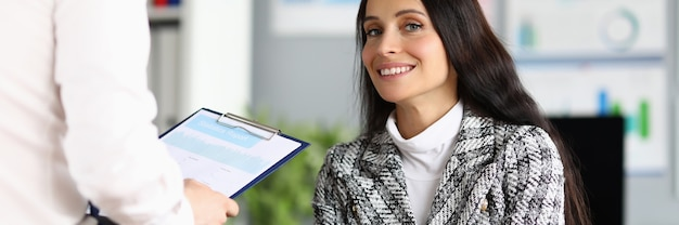 Beautiful woman with long hair in plaid jacket look and smile at workplace. man sit opposite director and hold folder with document in his hand.