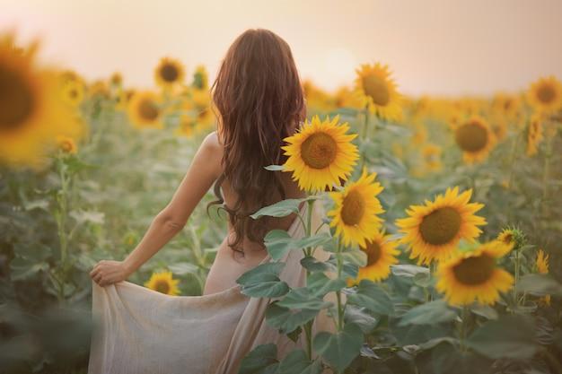 햇빛에 여름에 해바라기 밭에서 긴 머리를 섹시한 등을 가진 아름다운 여자