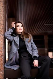 긴 머리를 가진 아름 다운여자가 앉아서 거리를 찾습니다. 모델 외모의 여자는 따뜻한 옷을 입고 앉아있다