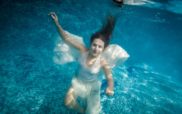 Beautiful woman with long hair swimming underwater at pool