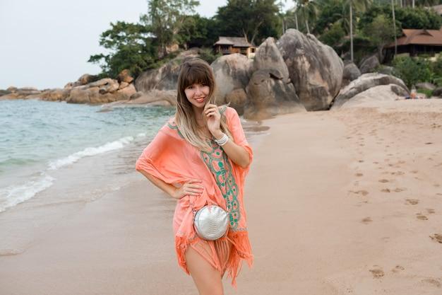 Красивая женщина с длинными волосами в стильном летнем платье бохо позирует на тропическом пляже.