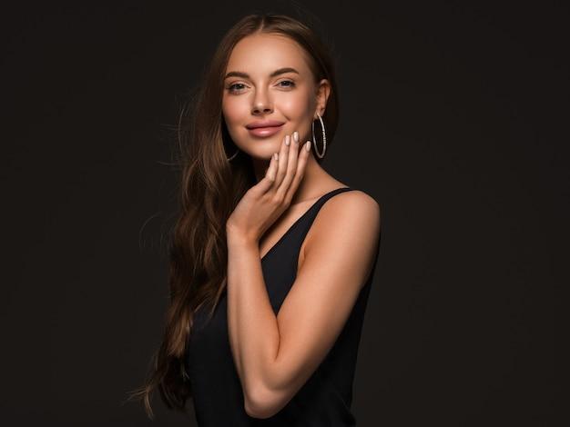긴 건강 한 곱슬 갈색 머리 귀걸이 검은 드레스 검은 배경에 아름 다운 여자