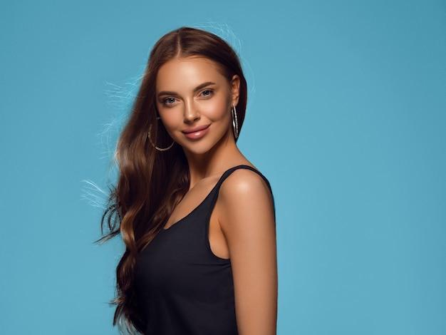 긴 건강 한 곱슬 갈색 머리 귀걸이 검은 드레스 색 배경 파란색으로 아름 다운 여자