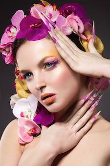 긴 손톱, 완벽한 피부, 난초의 머리카락을 가진 아름다운 여자. 스튜디오에서 촬영하는 초상화.