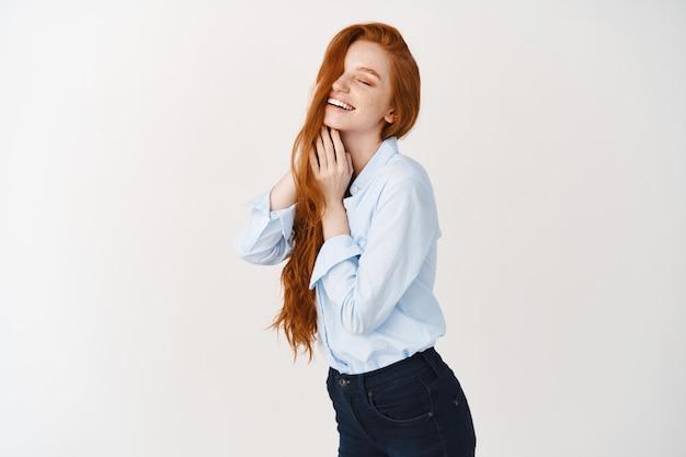긴 빨간 머리를 한 아름다운 여성, 기뻐하는 얼굴로 눈을 감고, 머리를 만지고, 흰 벽 위에 서 있는 아름다운 여성